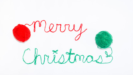 Merry Christmas Written in red and green Yarn with Balls of Yarn on Each Side. Photographed against a white background.