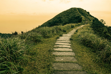 Fairy tale landscape and stepping stone path over a hill on the horizon at the Caoling Historic Trail in Taiwan