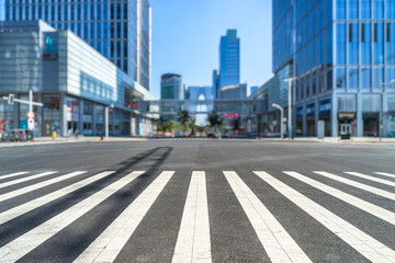 empty road with zebra crossing and skyscrapers in modern city.