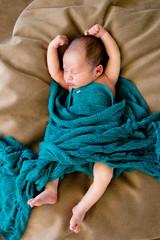 Sleeping Baby wrapped in green wool blanket on beige cushion