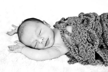 New Baby sleeping wrapped in crotchet wool blanket