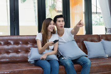 Young couple sitting and looking television