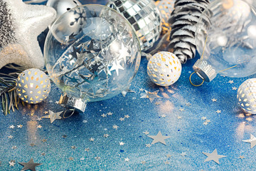 glass ball, holiday lights and silver cones for christmas tree decoration on blue background macro view