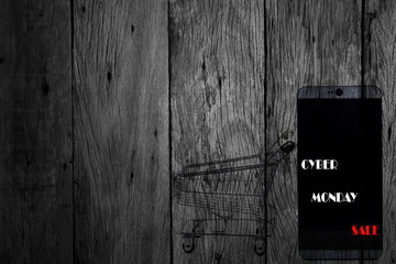 cyber monday sale text on mobile phone and shopping cart dark wooden background.