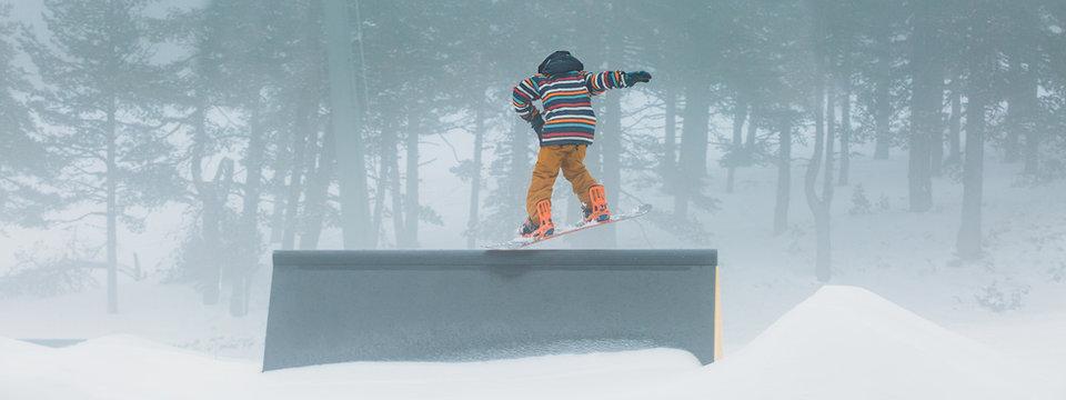 Skier doing snowboarding using a ramp