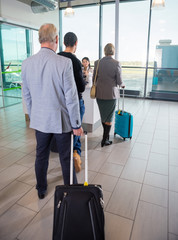 Passengers With Trolley Bags Waiting At Airport Reception