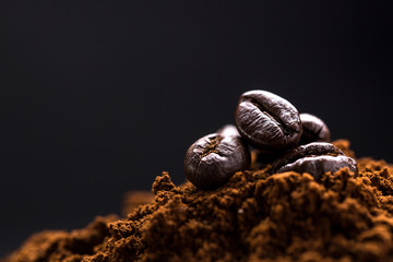 pile of ground coffee, and at the top several whole coffee beans.