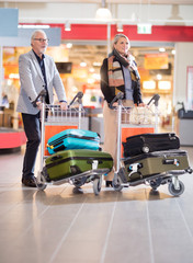 Senior Business Couple Walking With Luggage In Trolleys At Airpo