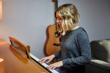 young blond woman playing piano