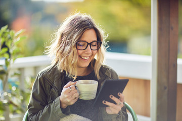 young blond woman with glasses reading tablet with coffee
