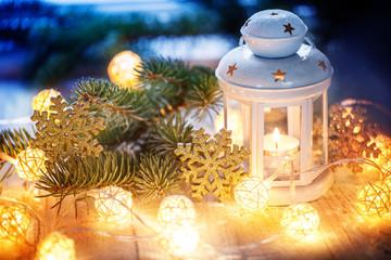 Christmas decoration with white candle lantern, fir tree branches and luminous garland.