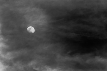 View of the moon through some clouds in the sky