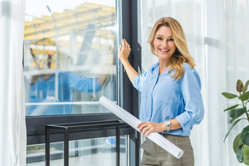 businesswoman with blueprint at window