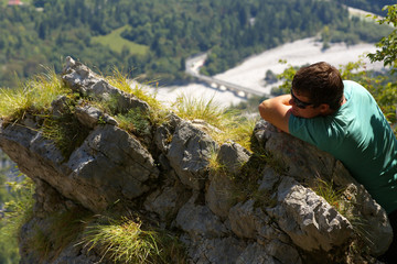 Resting man leaning against a rock with a valley on backroud, Slovenia