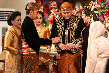Indonesia's President Joko Widodo looks at his daughter Kahiyang Ayu's wedding ring as his new son-in-law Bobby Nasution during their wedding cerem