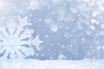 Big transparent snowflake in snow and beautiful bokeh with asterisks and snowfall.