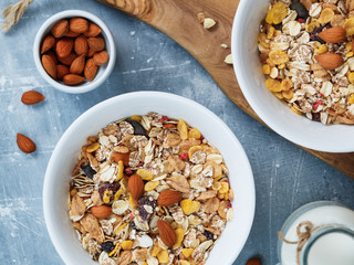 Top view of the breakfast for two person with muesli with almond nuts and dried berries in white bowls and milk on the blue textured table.