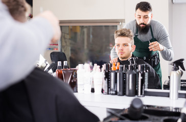concentrated guy stylist creating haircut for man client at hairdressing salon