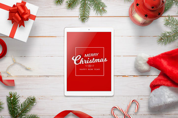 Top view of tablet with Merry Christmas message surrounded with Christmas decorations. Top view of white wooden desk.