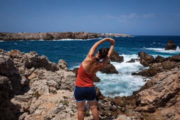 Mujer joven haciendo ejercicios de estiramiento frente al mar