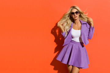 Sexy Blond Woman In Sunglasses, Violet Mini Skirt And Jacket