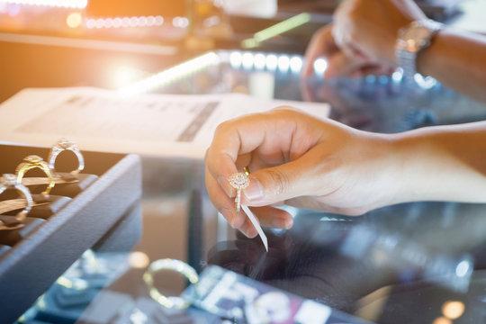 Asian woman choosing wedding rings at jewelry diamond shop