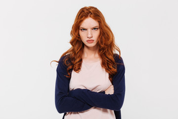 Angry pretty young redhead lady with arms crossed. Wall mural