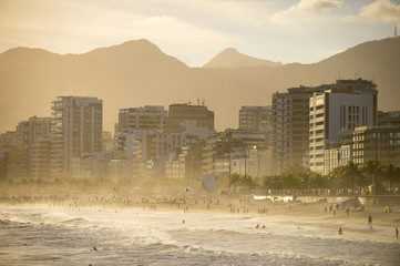 Silhouettes of people enjoing the golden misty sunset shores of Ipanema Beach in Rio de Janeiro, Brazil