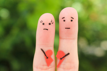 Fingers art of sad couple. Woman and man holding broken heart.