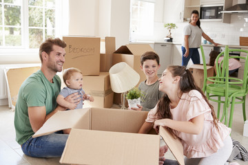 Children Helping Parents To Unpack On Moving In Day