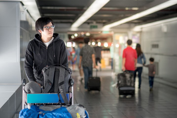 Young Asian man walking with airport trolley and his luggage in the international airport terminal, arrival from travel abroad
