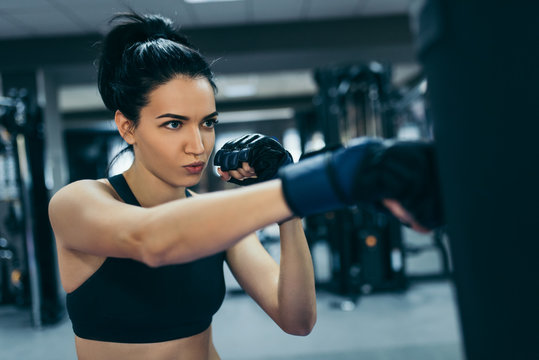 Side view of strong attractive brunette woman punching a bag with kickboxing gloves in the gym workout. Sport, fitness, lifestyle and people concept.