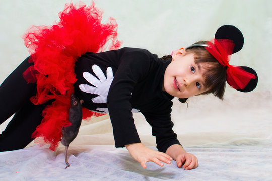 cute little girl in a bear costume with ears holds a hand rat