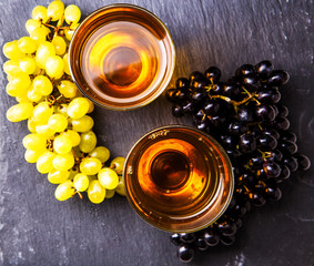 Image on top of two glasses with juice, black and green grapes