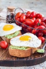 Open sandwich with mashed avocado and fried egg on toasted bread, sprinkled with black pepper, vertical
