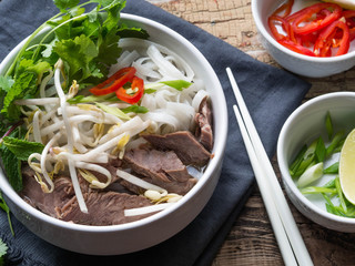 Traditional Vietnamese soup- pho in a white bowl with beef and rice noodles, mint and cilantro, green onion, chili, bean sprouts and lime on a wooden board background . Asian food.