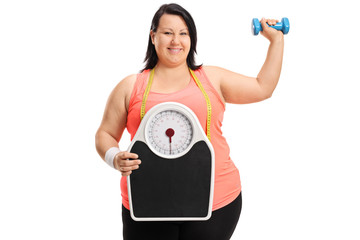 Joyful overweight woman with a weight scale and a small dumbbell