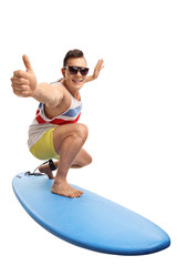 Young man surfing and making a thumb up gesture