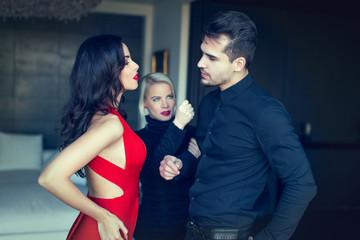 Angry woman threatens disloyal man flirting girl in red dress