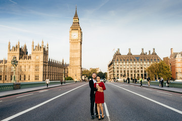 Beautiful city and people. Young family couple stand on Westminster bridge in background with Big Ben, enjoy free time together in London, have good relationships. City landscape background.