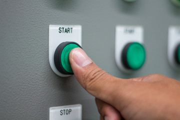 """The hand pressing """"start"""" switch on control board"""