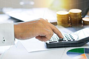 businessman press calculator and check business graph in paper workwith stacked of money coins .
