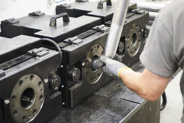 Inside a factory, industrial worker in action on metal machine