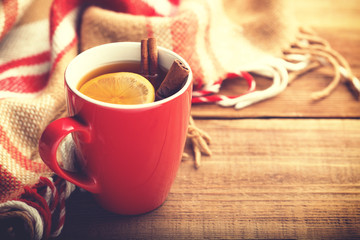 Red cup of hot tea with lemon and cinnamon.