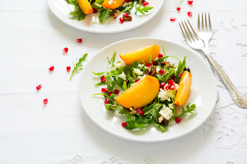 Fresh autumn salad with persimmon, arugula, cheese and pomegranate seeds on white table cloth. Space for copy