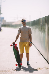 Portrait of confident young man with longboard