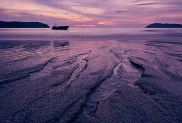 Sunset over Pantai Cenang beach with pink colours, blur background and silhouette of boat. Langkawi, Malaisiya.