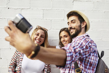 Three friends taking photos at white wall