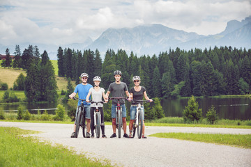 Family of four cycling near Kögelweiher, Pfronten, Bavaria, Germany