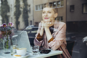Woman with her laptop enjoying the view in a cafe
